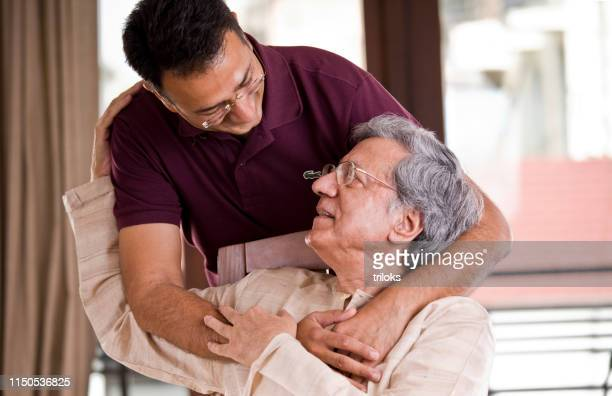 man spending time with his father at home - care stock pictures, royalty-free photos & images