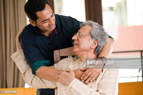 man spending time with his father at home - son stock pictures, royalty-free photos & images