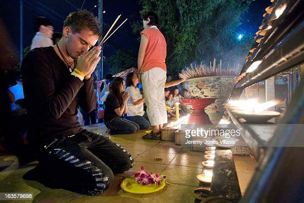 CONTENT] A man spends a moment of silence to honor the Buddha amidst the activities of the Yi Peng Festival in Chiang Mai Thailand