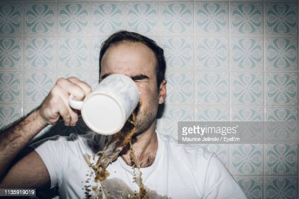 man spilling coffee while drinking at home - spilling stock pictures, royalty-free photos & images