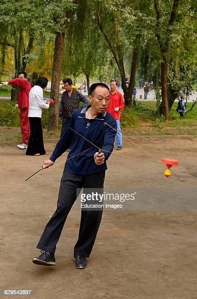 Man spinning a Chinese Yo Yo in Zizhuyuan Purple Bamboo Park in Beijing China