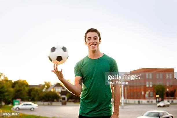Man spinning soccer ball on finger