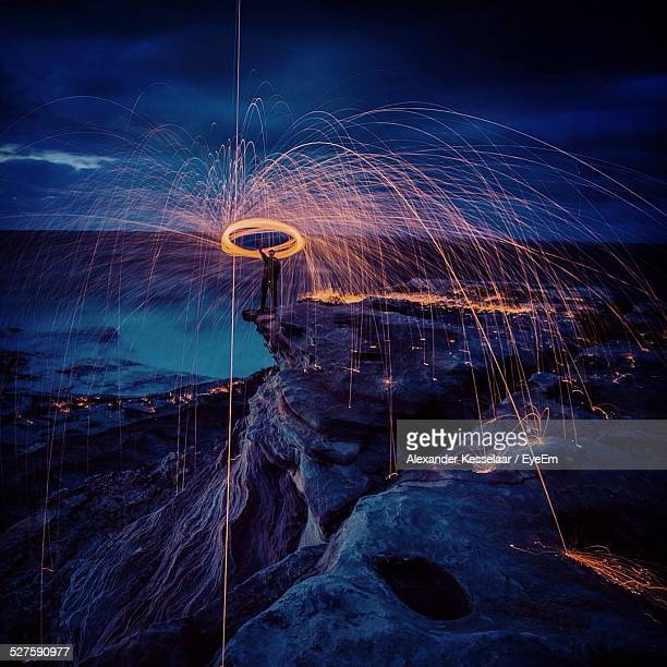 Man Spinning Steel Wool On Rock At Night