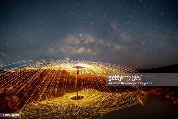 man spinning wire wool against star field at night - provincia di songkhla foto e immagini stock