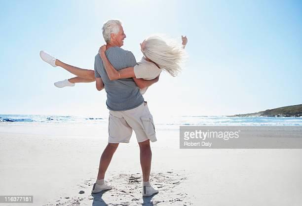 Man spinning woman on beach