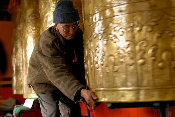A Man Spins A Massive Cylindrical Prayer Wheel At The Druk