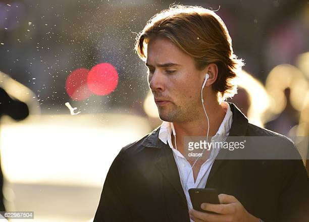 Man spitting and using mobile smart phone