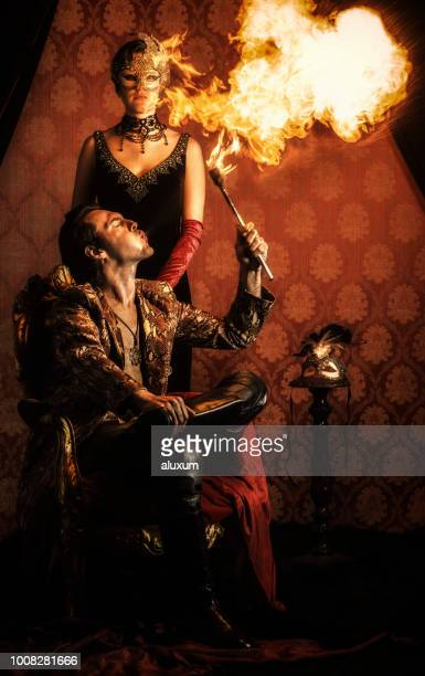 man spitting fire with mysterious woman wearing a venetian mask - circus stock pictures, royalty-free photos & images