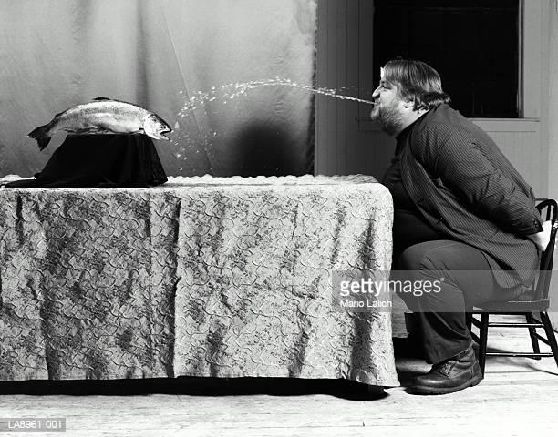 Man spitting water at fish (B&W)