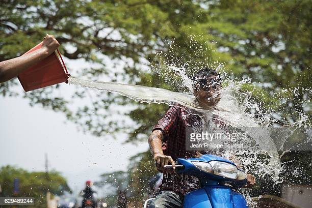 man splashed by a bucket of water while riding a motorbike on a Burmese road during Thingyan Water Festival, Myanmar's traditional New Year Festival, in April 2016