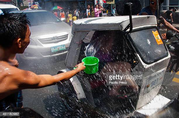 A man splashes water inside a tricycle with a passenger during the celebration of Wattah Wattah festival in San Juan City The annual festival in...
