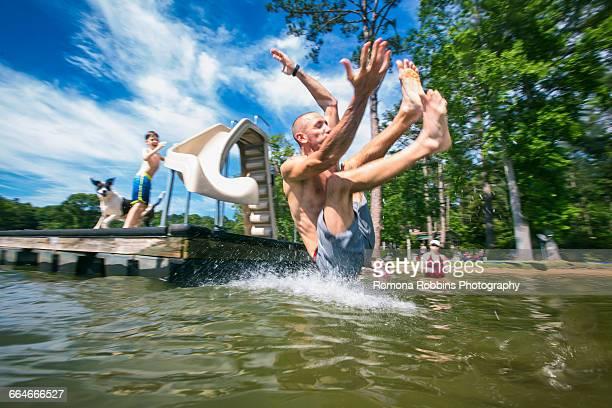 Man splashing into lake from pier slide at Jackson Lake, Georgia, USA