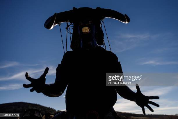 TOPSHOT A man sporting horns on his head and grease on his face to represent 'Diablos de Luzon' performs during the carnival in Luzon near...