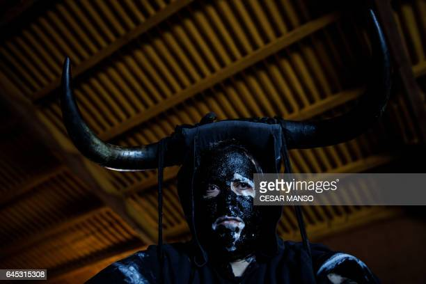 A man sporting horns on his head and grease on his faces to represent 'Diablos de Luzon' prepares during the carnival in Luzon near Guadalajara on...