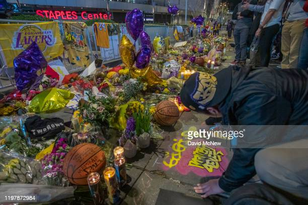 A man spray paints a memorial tribute near Staples Center before the first Lakers game since former NBA star Kobe Bryant and his 13yearold daughter...