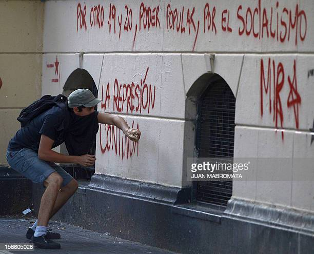 A man spray paints the walls of City Hall on December 20 2012 in Buenos Aires during a demonstration on the 11th anniversary of the clashes that took...