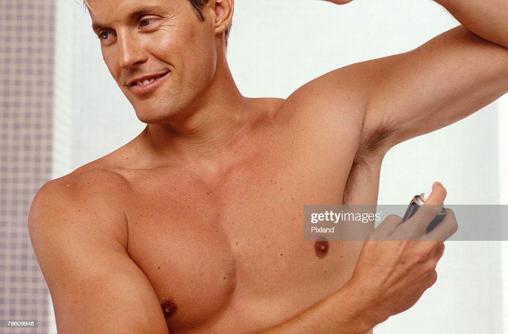 Man spraying antiperspirant : Stock Photo