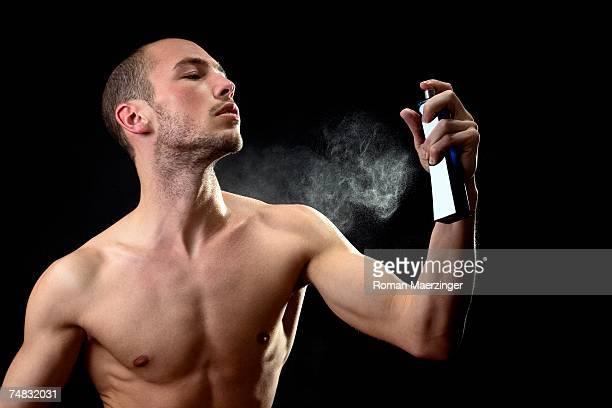 man spraying fragrance - chicos desnudos fotografías e imágenes de stock