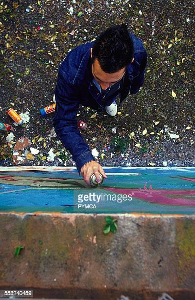 Man spraying graffiti on a wall from above UK 1990s.
