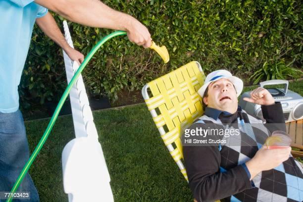 Man spraying neighbor with hose
