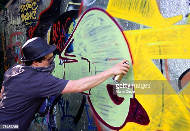 A man spraying paint on a wall