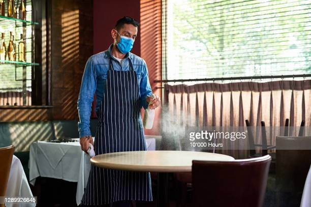 man spraying restaurant table with sanitiser - restaurant stock pictures, royalty-free photos & images