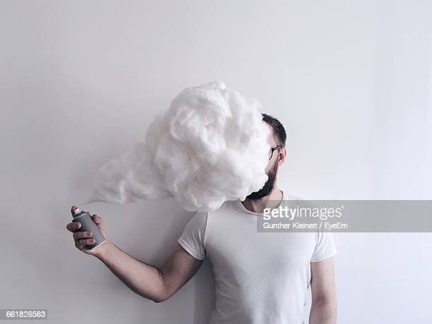 Man Spraying Shaving Cream In Front Of Face Against Wall