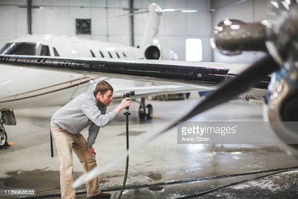 man spraying under an airplane wing - annie sprinkle stock pictures, royalty-free photos & images