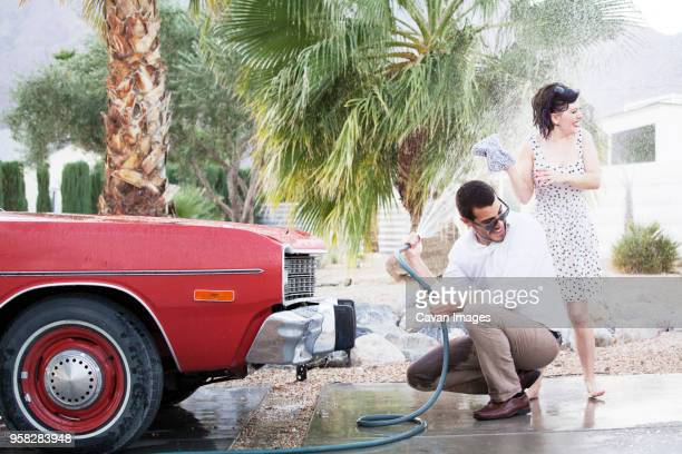 man spraying water on woman while washing car at parking lot - mid adult men imagens e fotografias de stock