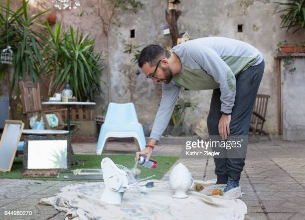 Man spray-painting decorative objects with white paint