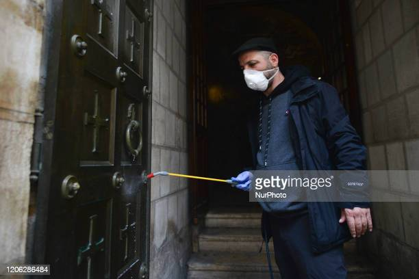 A man sprays a building entrance along the Via Dolorosa Street a processional route in the Old City of Jerusalem believed to be the path that Jesus...