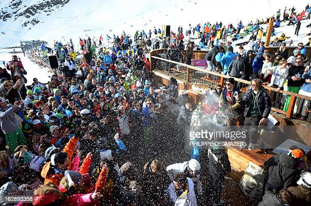A man sprays champagne as people drink and dance on an outdoor dance floor at the 'La Folie Douce' on February 28 2013 in Val Thorens French Alps 'La...