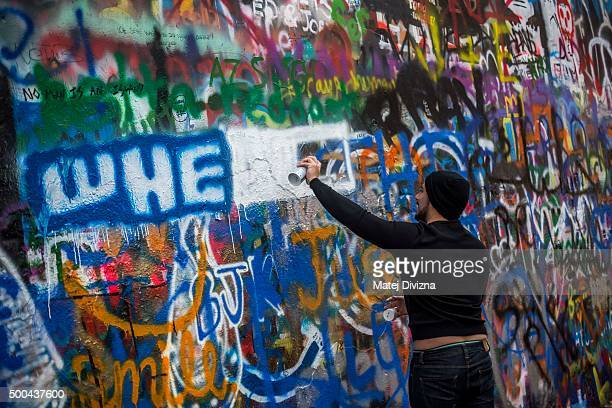 A man sprays graffiti on the Lennon Wall the memorial dedicated to the late John Lennon on the 35th anniversary of his death on December 8 2015 in...