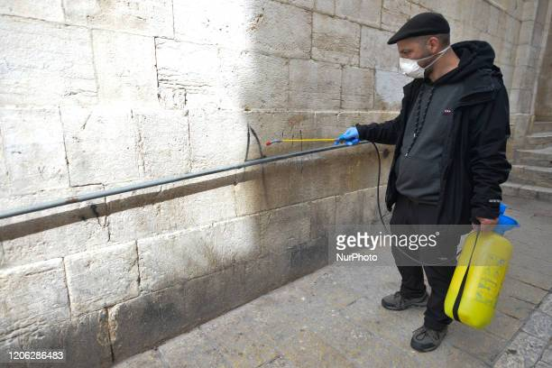 A man sprays handrail along the Via Dolorosa Street as local shop owners disinfect themselves all public places and entrances along a processional...