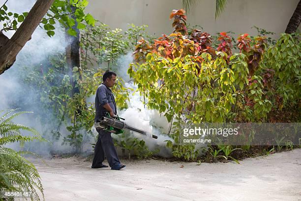 Man Sprays Mosquito Treatment at Resort