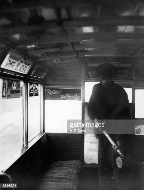 A man sprays the inside of a bus of the London General Omnibus Co with antiflu preparation during the flu epidemic which followed the First World War...