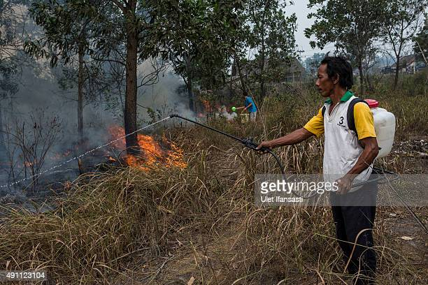 A man sprays the water as they extinguish the fire on burned peatland and fields near his house at Ogan Ilir district on October 3 2015 in Palembang...