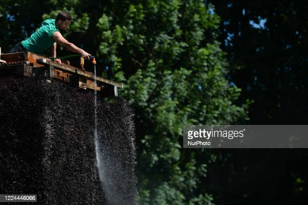 Man sprays with water the top of a newly opened Nowa Huta's graduation tower. On Wednesday, July 01 in Krakow, Poland.