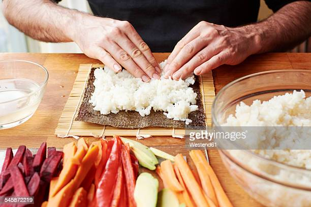 Man spreading rice on a nori sheet to make vegetable sushi