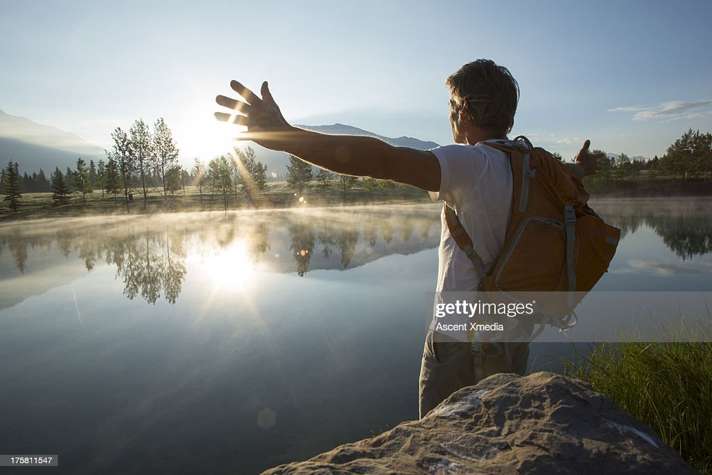 Man spreads arms wide across mountain lake : Stock Photo