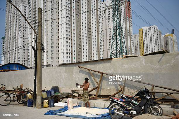 A man spreads rice grains on a sheet by the side of a road near the Green Bay Pluit residential and commercial project developed by PT Agung Podomoro...