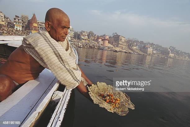 A man sprinkles flowers on the River Ganges at Varanasi India March 1997