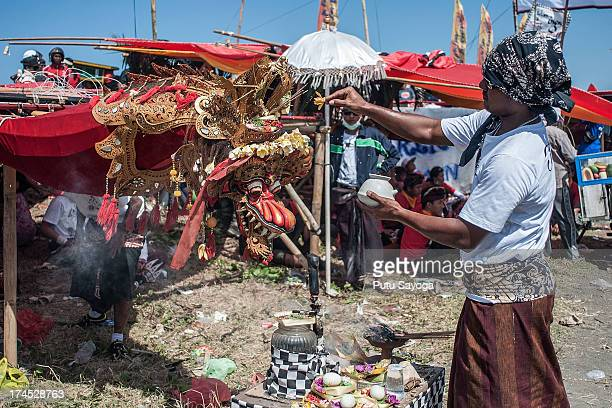 A man sprinkles holy water on the kite during Bali Kite Festival on July 27 2013 in Denpasar Bali Indonesia The event is a seasonal religious...