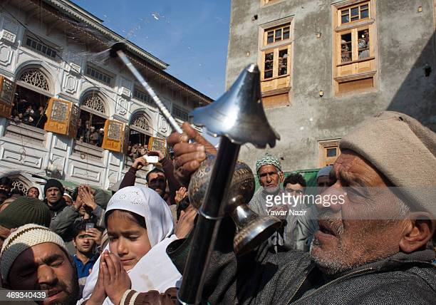 A man sprinkles rose water on Kashmiri Muslim devotees as a cleric displays a holy relic at the Dastgeer Sahib shrine during the Friday following...