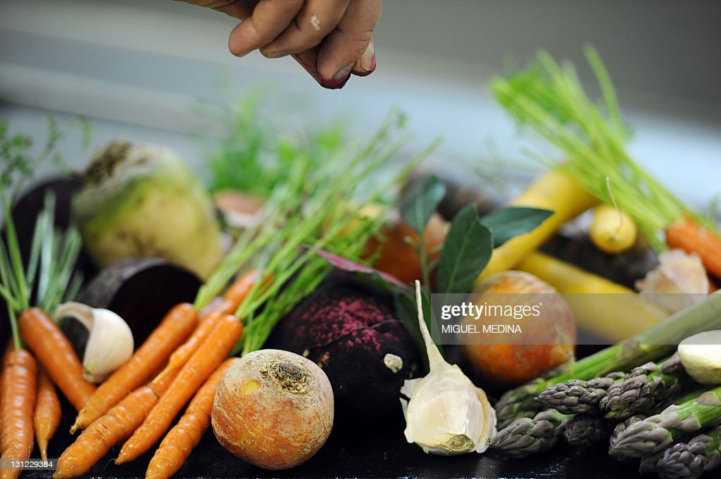 A man sprinkles spice on vegetables in a kitchen of French