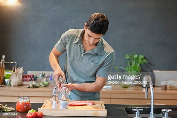 man sprinkling black pepper on the meat - pepper mill stock pictures, royalty-free photos & images