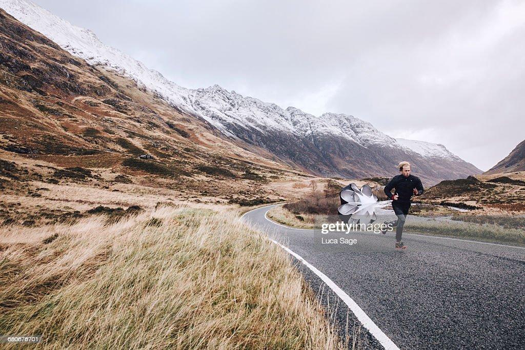 Man sprint training on a Scottish mountain road : Stock Photo