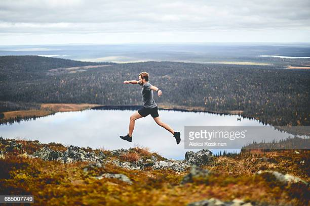 man sprinting on rocky cliff top, keimiotunturi, lapland, finland - cross country running stock pictures, royalty-free photos & images