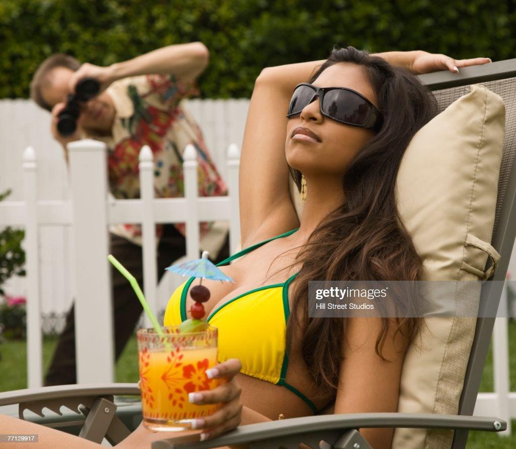 Man spying on Hispanic woman sunbathing : Stock Photo