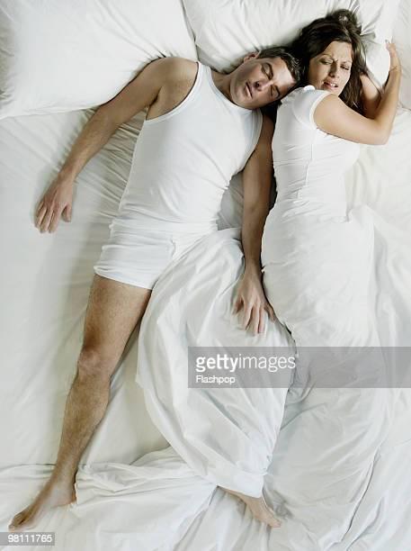 Man squashing woman in bed